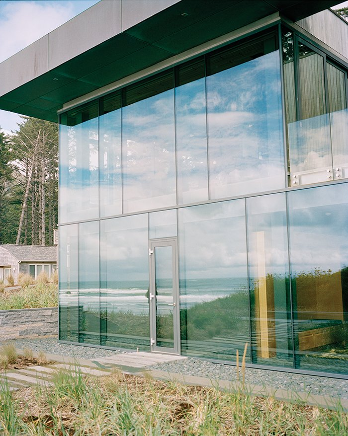 Exterior, Flat RoofLine, House Building Type, and Glass Siding Material Architects Stan Boles and Christopher Almeida arranged ten-foot-tall panes of glass in a steel curtain-wall frame to create the building's distinctive facade.  Photo 3 of 9 in Glass House with Stunning Pacific Ocean Views