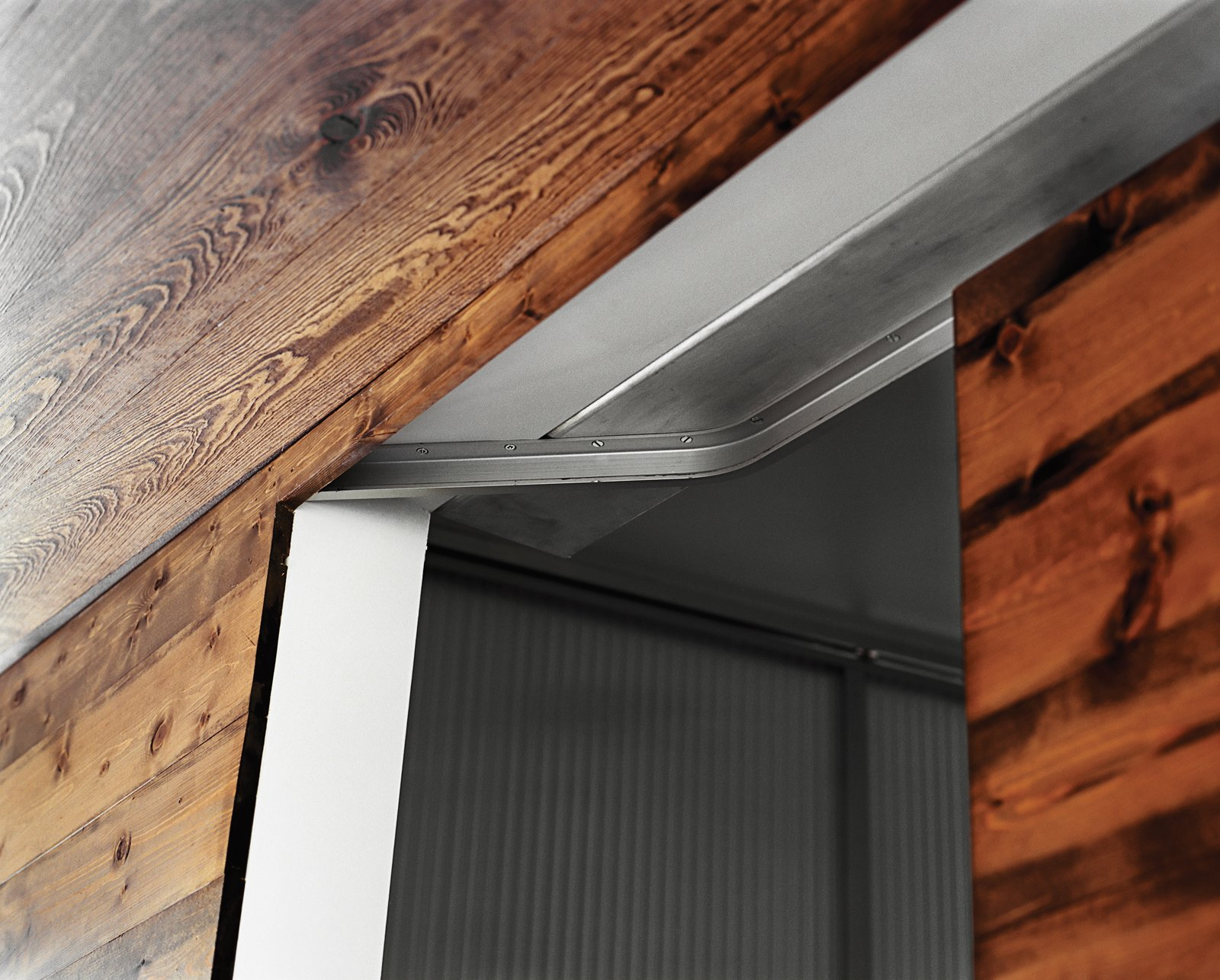 A close-up of the sliding door track shows the industrial detail of the recessed hardware.  New Grass Roots by Dwell