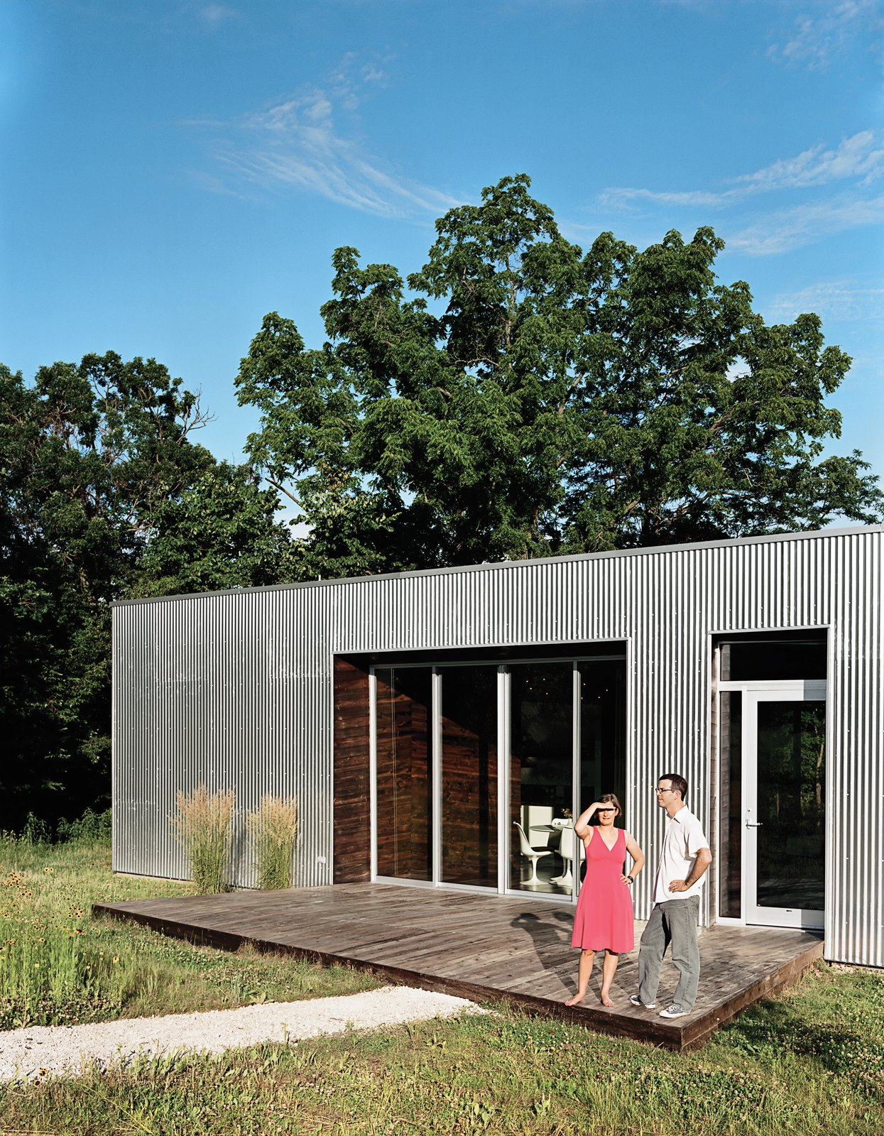 Exterior, Cabin Building Type, Flat RoofLine, House Building Type, and Metal Siding Material The front deck, invisible from the road, is an extension of the wood paneling in the main living space.  New Grass Roots by Dwell