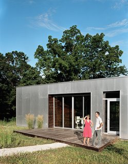 The front deck, invisible from the road, is an extension of the wood paneling in the main living space.