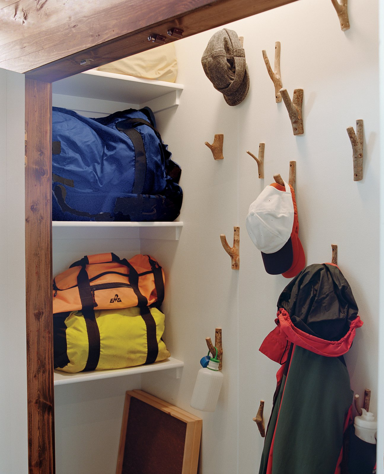 Storage Room and Closet Storage Type In the closet stick-like wall hooks continue the rural motif.  New Grass Roots by Dwell