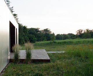 The design for the exterior of the house keeps things super simple—a small deck bridges the door with the grassy meadow, but allows the meadow itself to be the focus of the home's outdoor space.