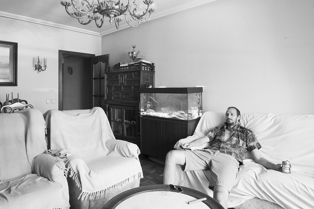 Vázquez poses in the pre-renovated living room.  Photo 3 of 10 in A Childhood Home in Madrid Grows Up