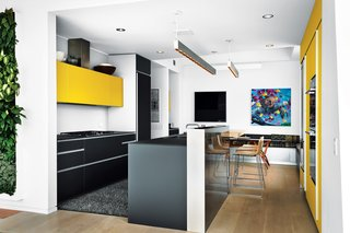 Geraldine and Kit Laybourne remodeled the kitchen in their High Line apartment with yellow and gray interiors. The kitchen features an Artematica Vitrum glass system from Valcucine, artwork by Craig Kucia, and banquette cushion fabrics by Hella Jongerius for Maharam.