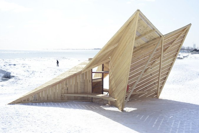 Driftwood Throne: DM_Studio (London)  Standing like a sentry on the beach, this angular sculpture assembled from reused timber hides a small bench below a raised viewing platform.  Modern Winter Retreats from Mini Structures Are the Winter Equivalent of the Lifeguard Station