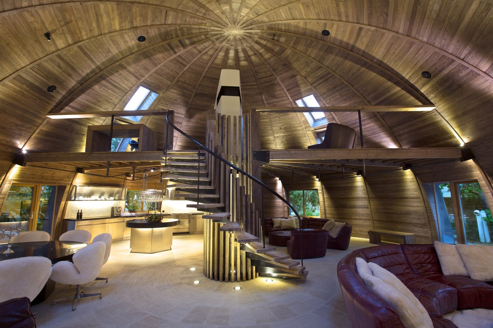 The Dome Home is divided into separate areas where designers can gather or break off to explore ideas. In the loft, a wooden desk blends seamlessly into its wooden environs. Meanwhile, on the lower level Timothy Oulton Shabby sofas with cushions made of real sheepskin off-cuts provide a comfortable place to congregate.  Photo 3 of 8 in A British Furniture Brand Built This Round Village in China