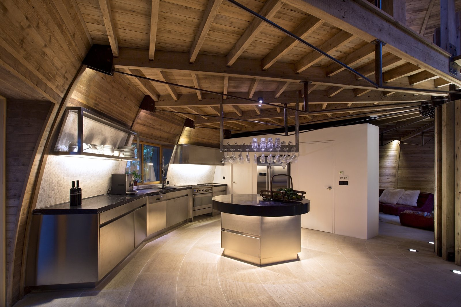 A full-service kitchen is nestled under the dome's loft. Clad in stainless steel, its custom-made cabinets match the appliances and the wine glass holder that hangs over the island. The kitchen's black marble countertops echo the surface of the dining table.  Photo 5 of 8 in A British Furniture Brand Built This Round Village in China
