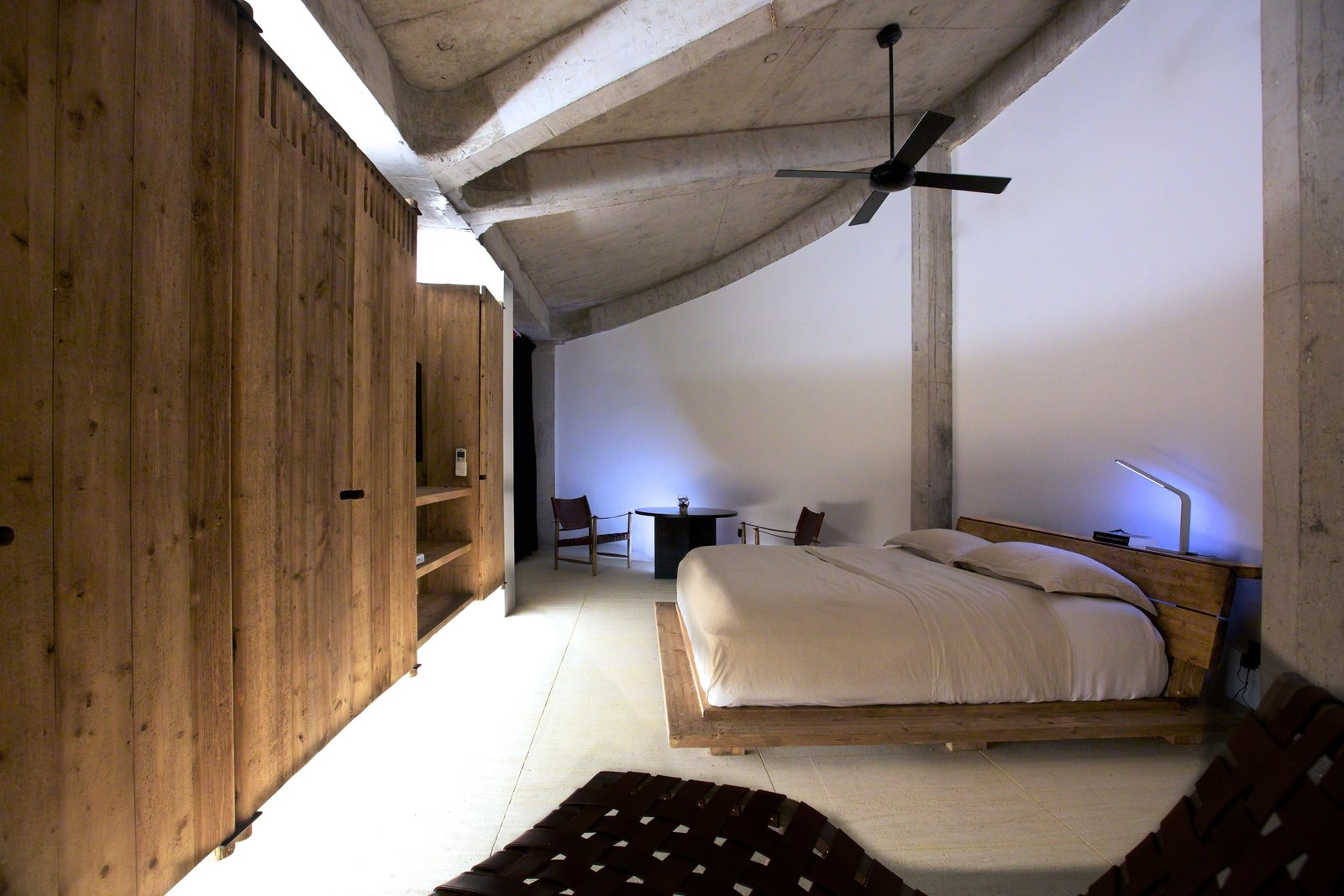 The Round Houses feature sleeping quarters outfitted with Timothy Oulton Brigadier mattresses and covers. The bed and wardrobe unit were both custom-made using reclaimed pine. Beyond the bed, a Halo Brussels armchair and marble coffee table serve as a space for private contemplation and relaxation.  Photo 7 of 8 in A British Furniture Brand Built This Round Village in China