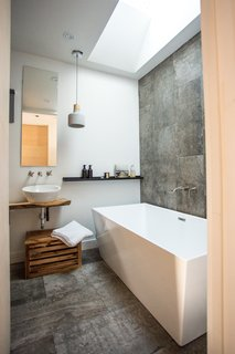 In the bathroom, the sink is mounted on salvaged live-edge wood.