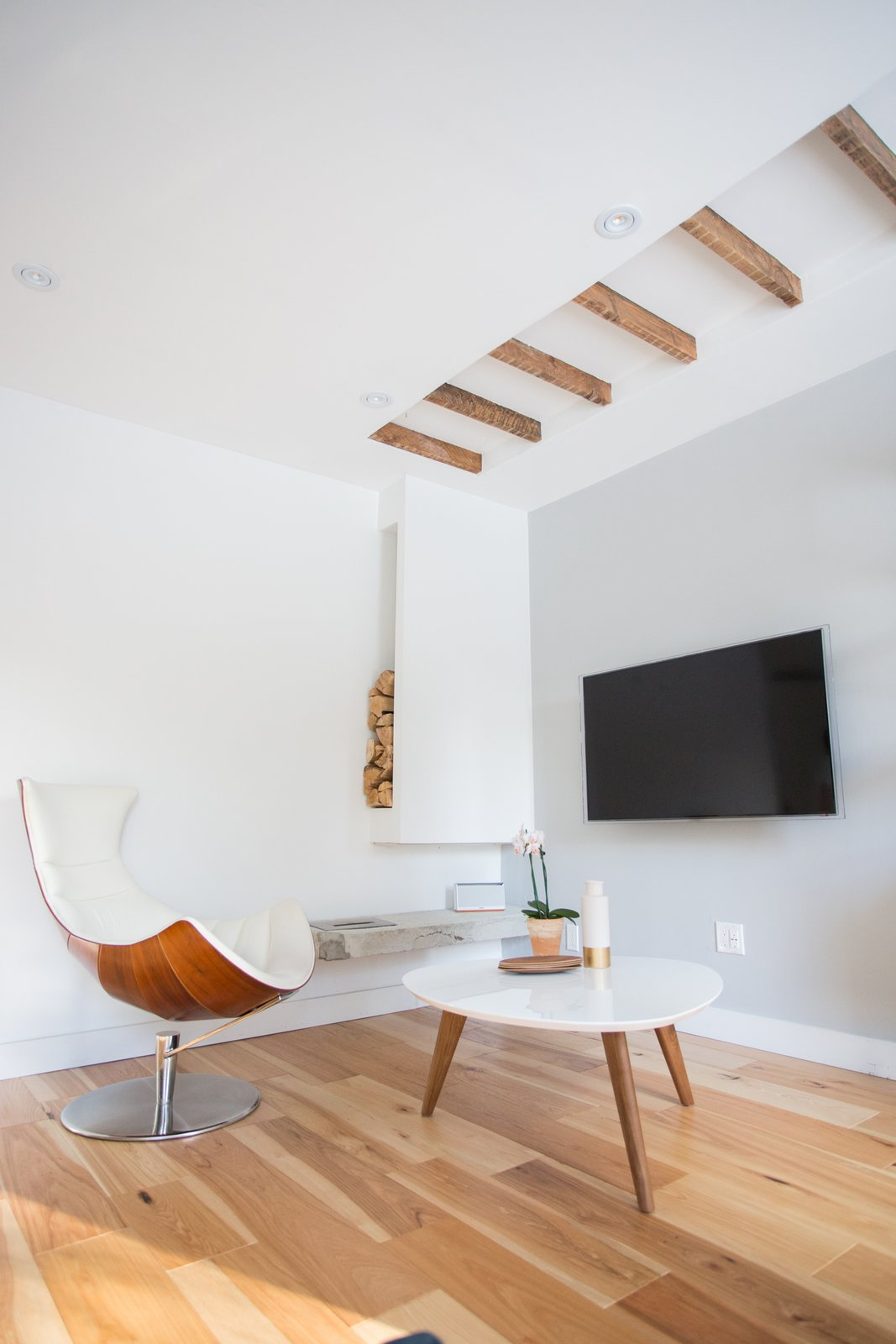 Living Room, Chair, Coffee Tables, and Medium Hardwood Floor In lieu of a fireplace, the pair opted for an exposed ethanol burner mounted on exposed concrete (the wood is just decor).  40+ Homes With Exposed Beams: Rustic to Modern by Luke Hopping from A Toronto Couple Renovates Their 675-Square-Foot Dream Home