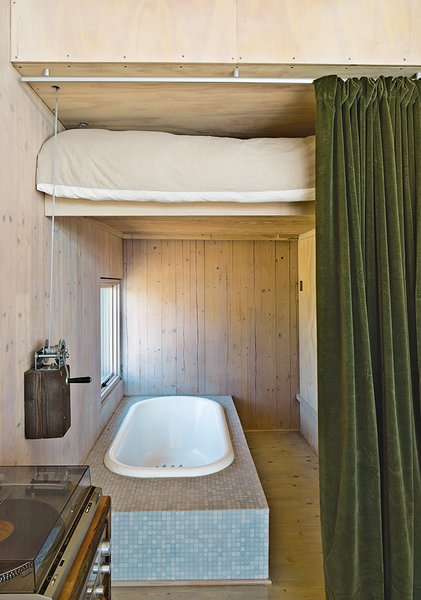 Taking inspiration from train cabins, the guest bed lifts to reveal a bathtub. Garlick made the mechanism using sailboat hardware. The velvet curtain is by Restoration Hardware and the tile is from Stone Tile.