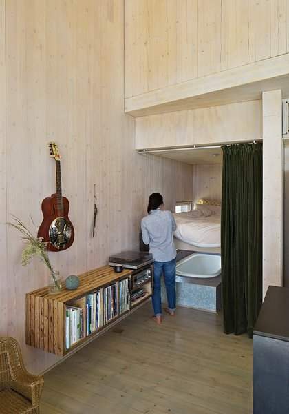 The floating bookshelf is composed from wood found on the property. Garlick purchased the Technics turntable and receiver from a used audio store.