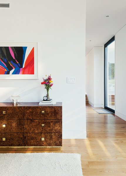 The 1970s burlwood dresser is originally from a Palm Beach estate. Modernist sculptures throughout the house are by artist Costantino Nivola; abstract artwork is by Charles Schorre.