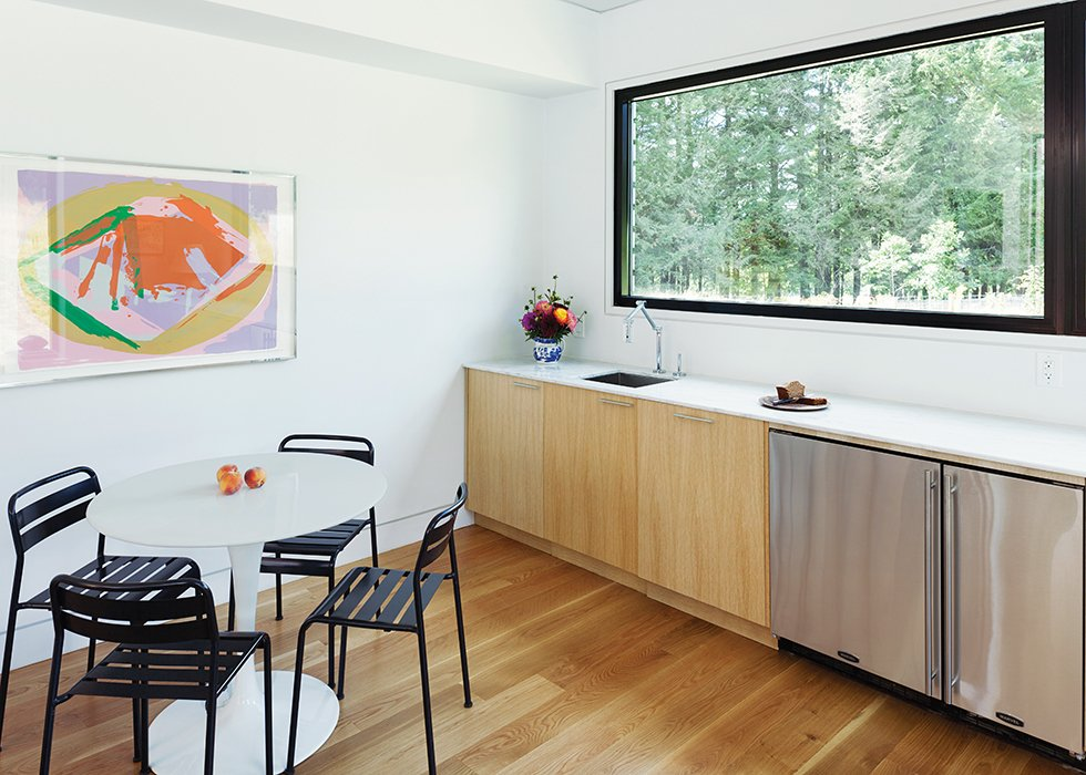 Dining Room, Table, Chair, and Light Hardwood Floor LABhaus designed the custom cabinetry for the mini-kitchen in the great room; the articulated faucet is by Kohler.  Photo 4 of 11 in Cute Couple Alert: Modern Prefab Poolhouse Addition to a 1920s Sears Kit House