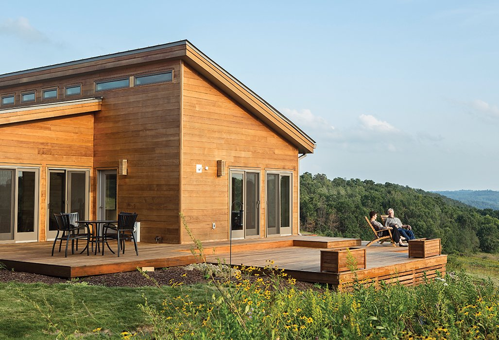 Exterior, House Building Type, Prefab Building Type, and Shed RoofLine Karen Ellzey and Tim Wright gaze at the hills of Wisconsin's Driftless Area from the deck outside their prefab house by Blu Homes. The Brant Natural Folding Chairs are from Crate and Barrel, and the Strata chairs and wrought-aluminum patio table are by Summer Classics.  Houses from Grandson of Frank Lloyd Wright Constructs Peaceful Prefab Near the Legend's Famed School