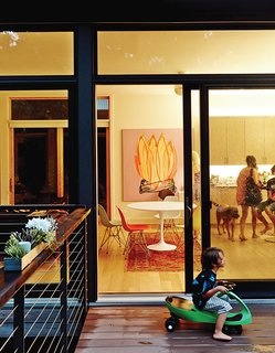 Glass doors make for an easy transition from the deck to the kitchen, where a painting by Erin Rachel Hudak hangs behind a round Saarinen dining table.