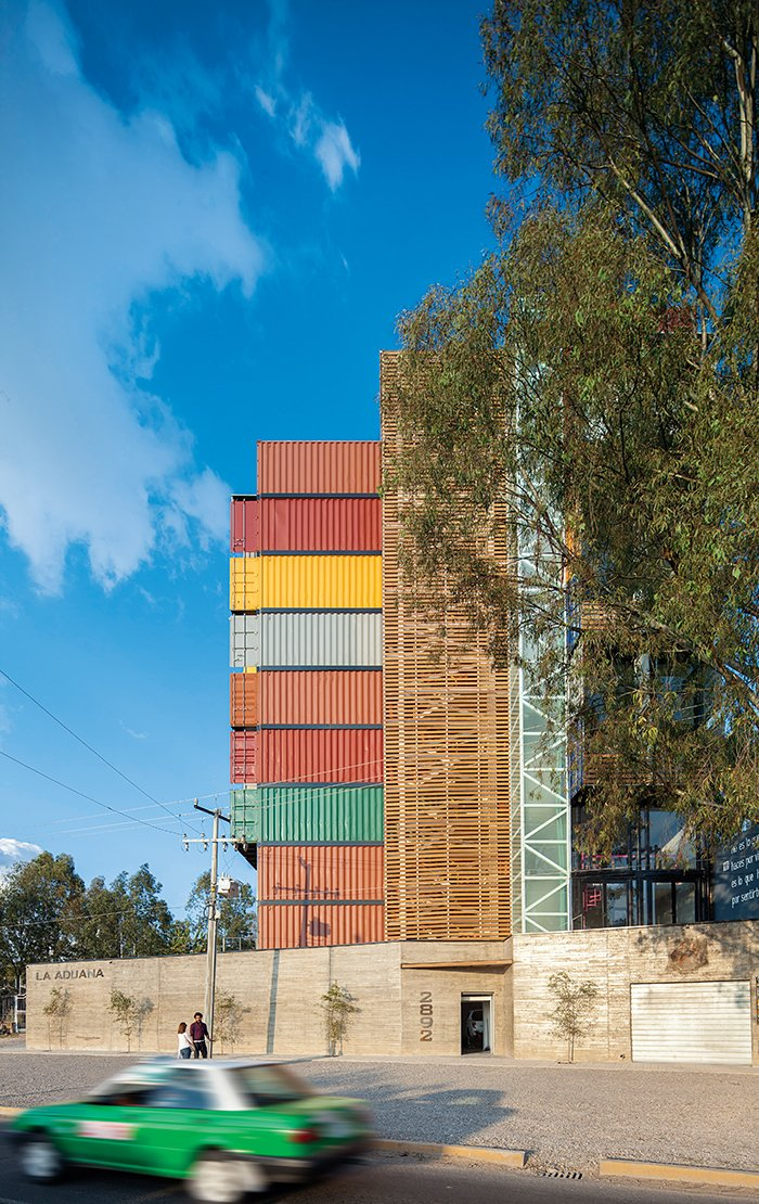 Exterior, Apartment Building Type, and Shipping Container Building Type The exposed wooden stairwell creates a warm contrast with the concrete and metal used elsewhere.  Photo 1 of 2 in Stacked Shipping Container Apartment from Adventurous Apartment Building Made of 36 Shipping Containers