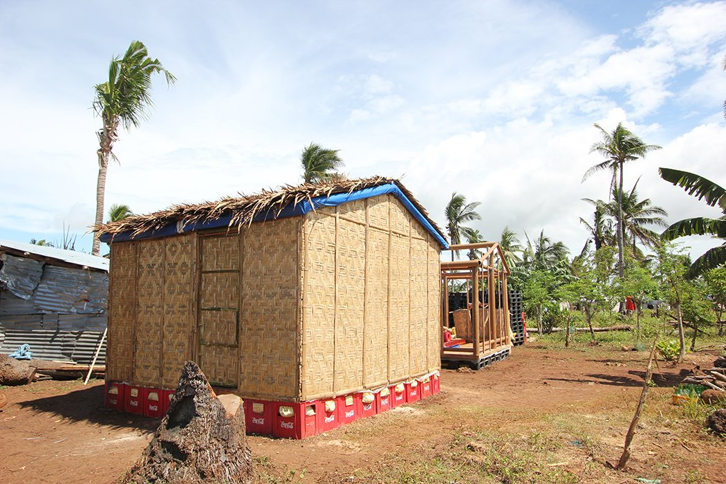 Soda crates serve as a foundation and prevent the structure from taking on water, as does the heavy-duty plastic beneath the thatch on the roof.  Photo 3 of 5 in Shigeru Ban Designs Temporary, Easy-to-Build Shelters for Disaster-Prone Areas