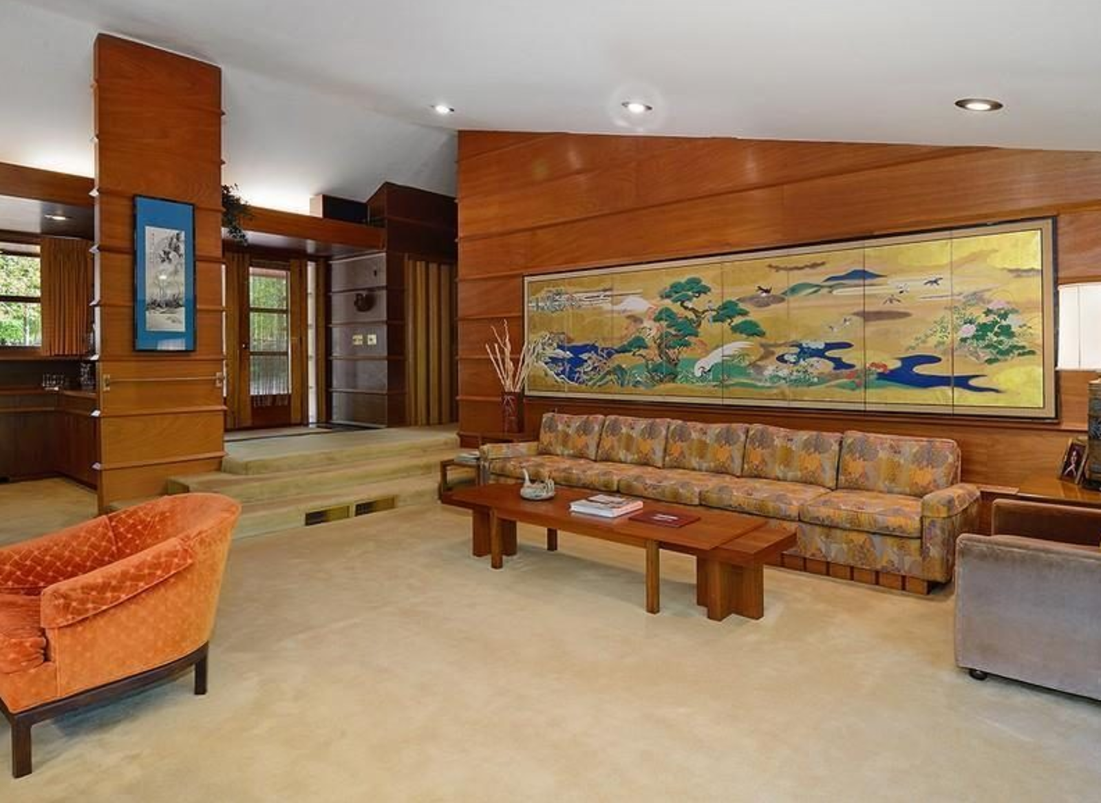 """Living Room, Sofa, Chair, Coffee Tables, Ceiling Lighting, and Recessed Lighting Another house built from Wright's Prefab #1 plan for Marshall Erdman & Associates, the Socrates Zaferiou House in New York state, was sold in 2014.   The Prefab #1 layouts, which ranged in size from 1,800 to 2,400 square feet, shared a single story, L-shaped plan with a """"pitched-roof bedroom wing joining a flat-roofed living-dining-kitchen area centered on a large masonry fireplace."""" Alongside prefabrication managed by Erdman's company, the architect sourced off-the-rack Andersen windows and Pella doors and used basic materials like plywood and Masonite to cut costs. [Photos via Curbed]  Photo 3 of 6 in A Look at Frank Lloyd Wright's Little-Known Prefabs"""