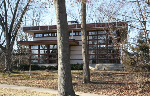 The Rudin House in Madison, built following Lloyd Wright's prefabricated Plan #2 for Marshall Erdman's company, is one of two homes built as a large, flat-roofed square with a double-height living room accented with a wall of windows. [Photo via Mike Condren]