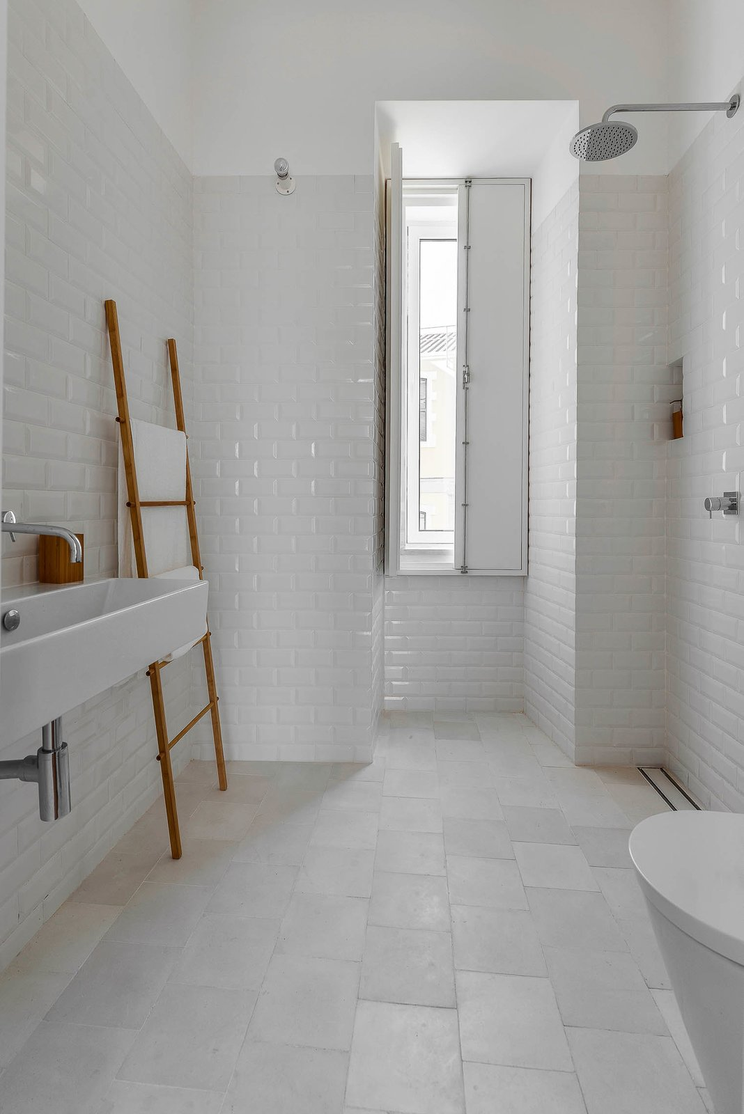 """Bath Room, Open Shower, Wall Mount Sink, and Subway Tile Wall White tiles — hydraulic ones on the floor and """"biselado"""" (meaning """"beveled"""") ones on the walls — make for a tranquil bathroom.  Best Photos from Minimal Apartment in Lisbon Divvied Up by Sliding Doors"""