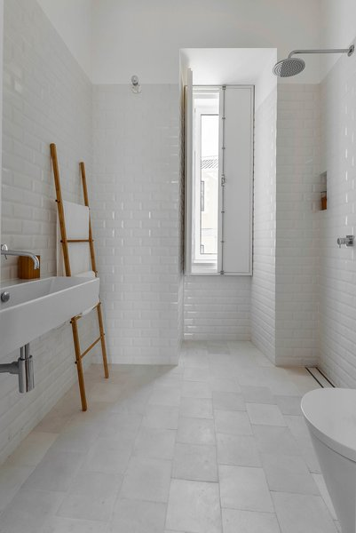 "White tiles — hydraulic ones on the floor and ""biselado"" (meaning ""beveled"") ones on the walls — make for a tranquil bathroom."