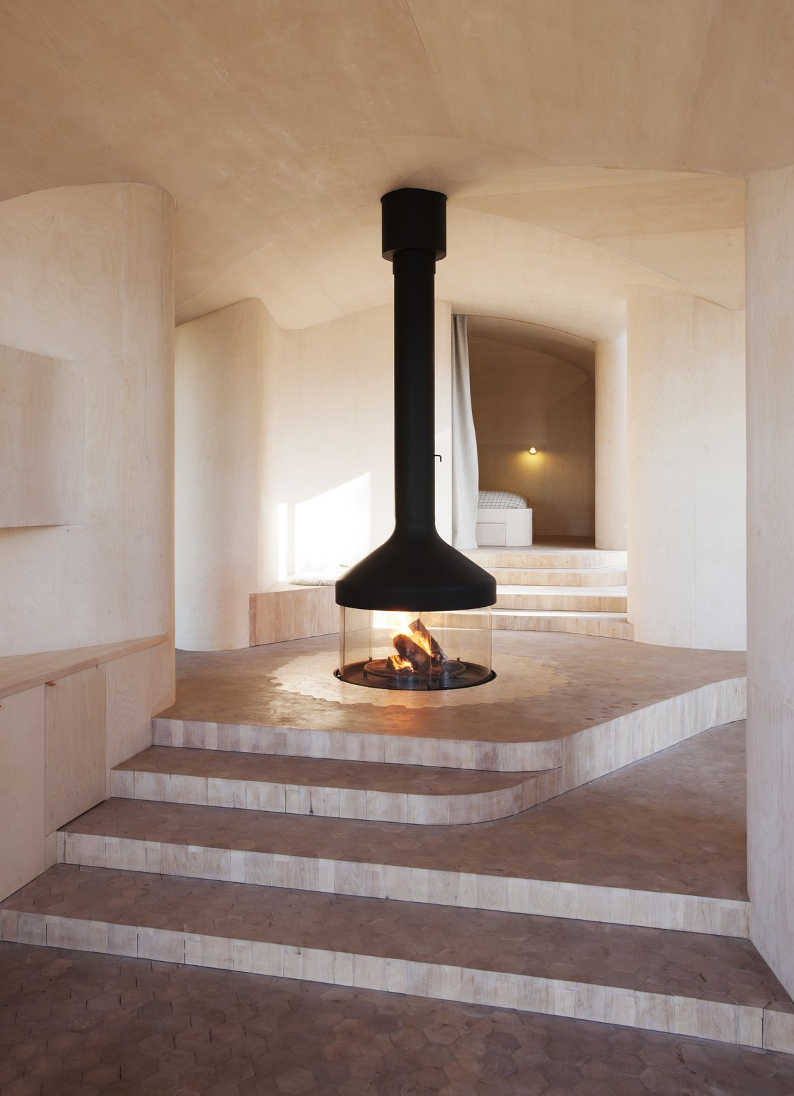 "Living Room, Hanging Fireplace, and Marble Floor Atelier Oslo overcame nature's challenges when they designed Cabin Norderhov, a seasonal, eco-friendly retreat on a steep hillside overlooking Lake Steinsfjorden. The home's layout revolves around a central glass and metal ""campfire"" that burns beneath a suspended mantel. Since it's located at the access level, the fireplace's flickering warmth can be enjoyed throughout the house. The surrounding floor is covered with hexagon tiles cut from marble, which transition into tiles made of birch log in the rest of the house.  97+ Modern Fireplace Ideas from Cabin Norderhov"
