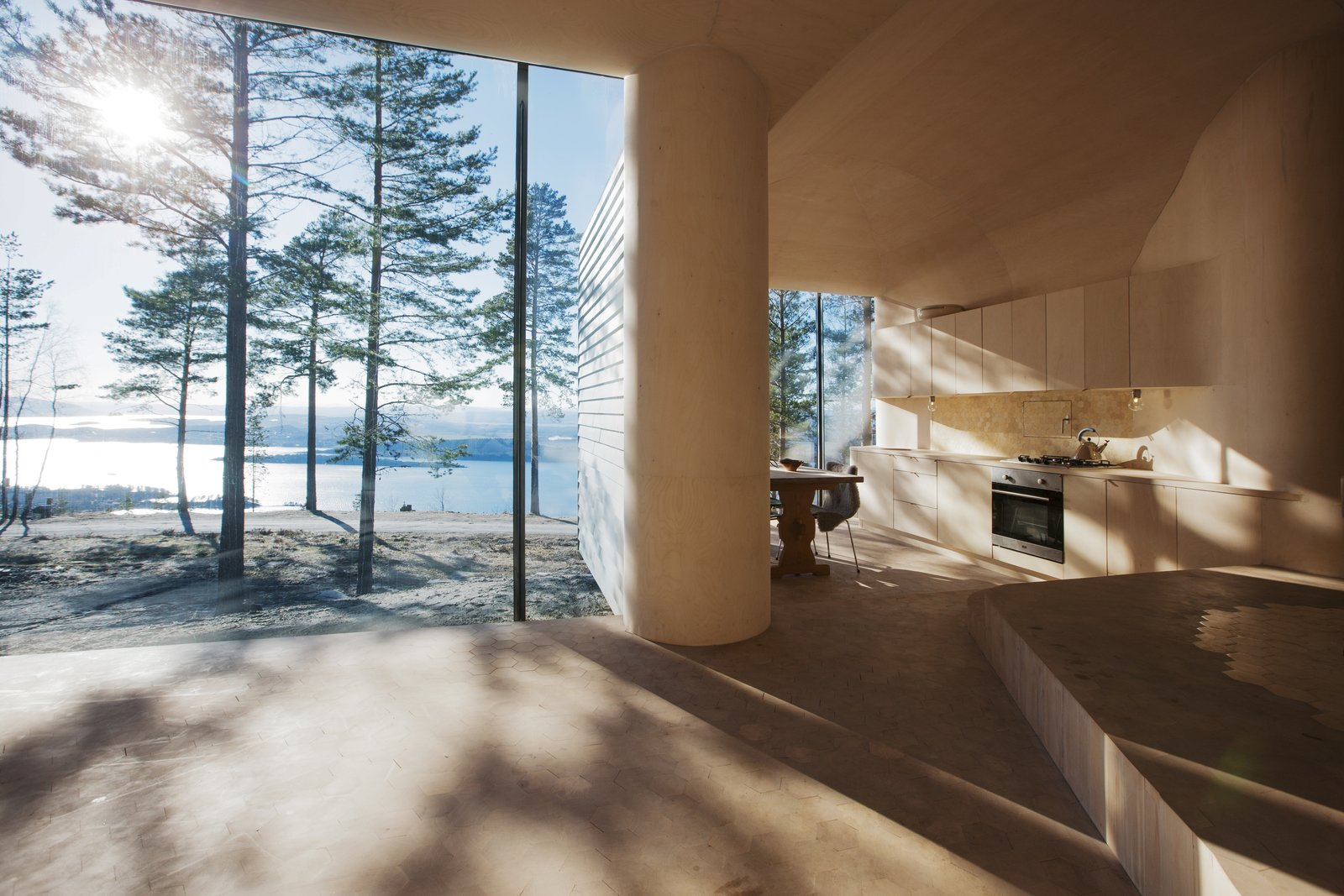 """The architects designed the large glass expanses in the dining and living areas so that their frames are hidden from view. """"I love the way the light comes into the cabin and meets the curved surfaces of the walls and ceilings,"""" Bae Brandtzæg says. The kitchen's custom cabinets were designed by Atelier Oslo and constructed by the contractor, Byggmester Bård Bredesen. The gas-powered stove, oven, and fridge are by VERA.  Sweden"""