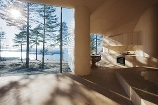 """The architects designed the large glass expanses in the dining and living areas so that their frames are hidden from view. """"I love the way the light comes into the cabin and meets the curved surfaces of the walls and ceilings,"""" Bae Brandtzæg says. The kitchen's custom cabinets were designed by Atelier Oslo and constructed by the contractor, Byggmester Bård Bredesen. The gas-powered stove, oven, and fridge are by VERA."""