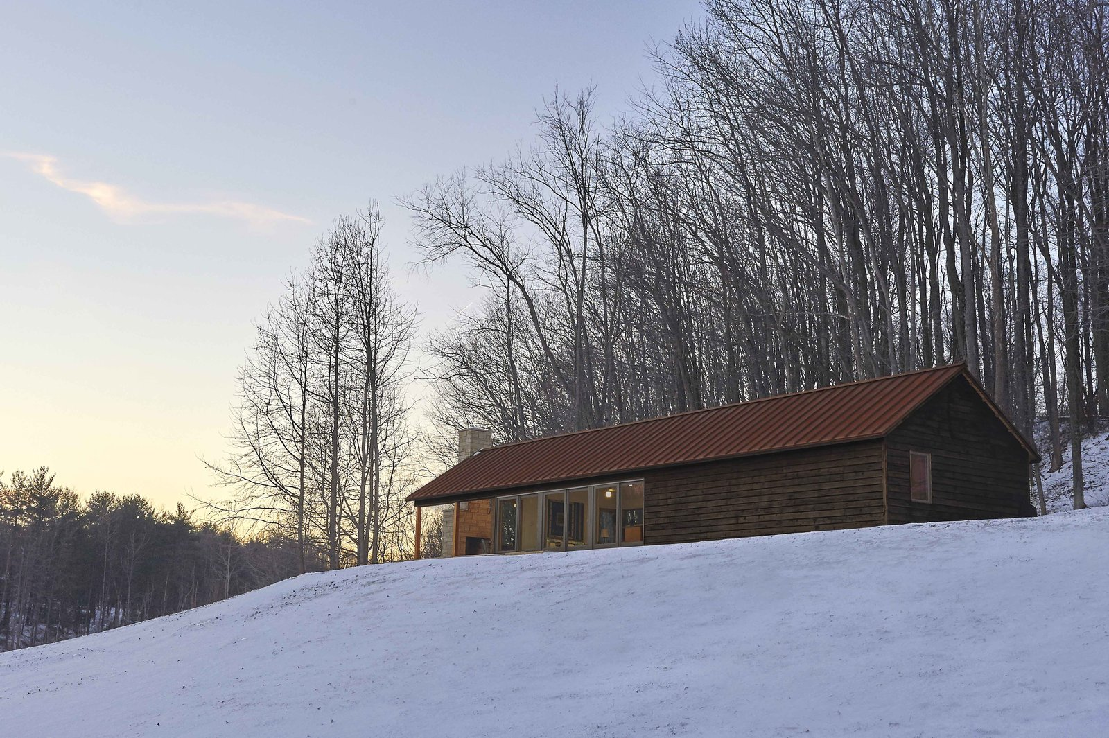 Durability was an important factor in the building's exterior. The architect selected materials, such as weathering steel for the roof and charred cedar for the siding, which would age gracefully. The deep browns and reds also blend into the forested landscape.  Off-Grid Retreat by Zachary Edelson