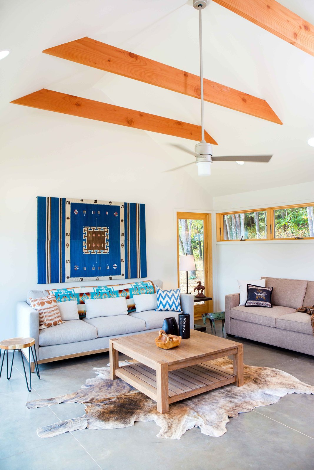 The bright ochres of the Douglas Fir beams and window framing accent the gray and white hues of the furniture, floors, and walls.  Off-Grid Retreat by Zachary Edelson