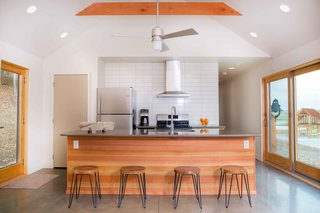 The kitchen island, also Douglas fir, showcases the material's rich striations and color variations. Behind the kitchen are two bedrooms and a single bathroom. A large open air pavilion, built concurrently with the cabin, can be seen from the windows on the right.