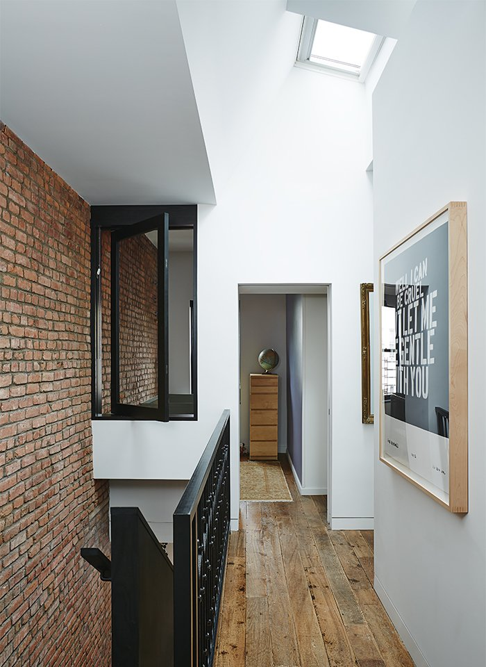 Hallway and Medium Hardwood Floor An interior window creates flow between the skylit landing and baby Banks's room.  Photo 10 of 14 in Brooklyn Home Keeps its Historic Bones While Getting a Much Needed Interior Update
