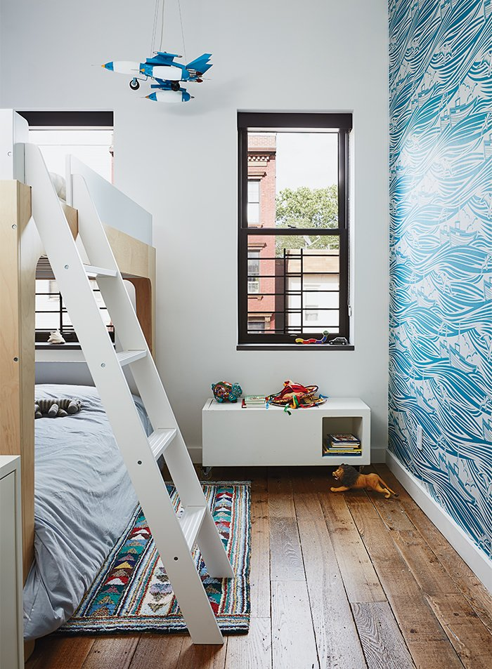 Kids, Night Stands, Bed, Neutral, Bunks, Bedroom, Rug, and Dark Hardwood Magid selected lively Whitby wallpaper by Mini Moderns for Linus's room, along with Oeuf's Perch bunk bed. The homeowner found the light-up rocket-ship mobile on a trip to Mexico City.  Kids Neutral Rug Dark Hardwood Photos from Wallpaper That Fixes Walls