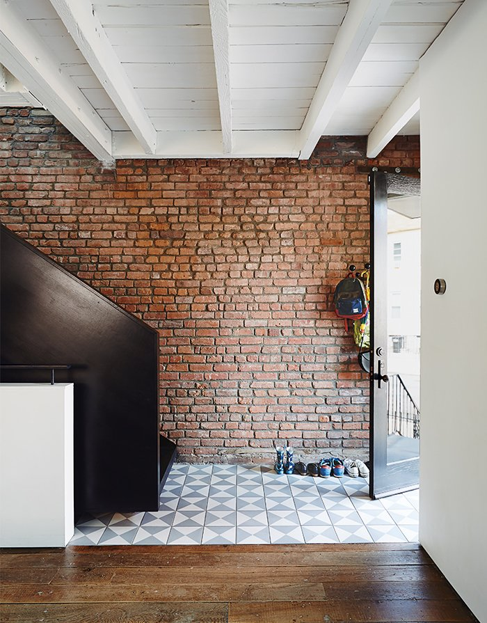 "Hallway and Dark Hardwood Floor Blackened steel for the Noroof-designed minimalist staircase matches the living room's ""Breuer"" window; reclaimed ash flooring came from a demolished church in Ohio.  Photo 13 of 14 in Brooklyn Home Keeps its Historic Bones While Getting a Much Needed Interior Update"