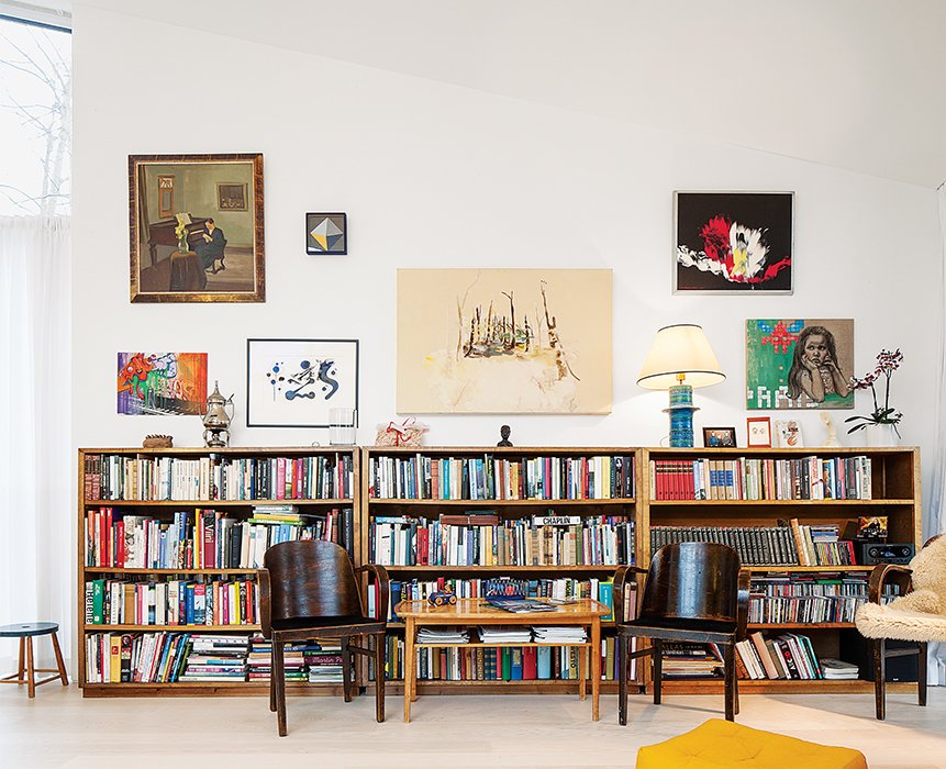 Living Room, Bookcase, Coffee Tables, Chair, Storage, Light Hardwood Floor, and Table Lighting The bookshelves lining the walls of the living room were inherited from family.  30+ Modern Homes With Libraries by Matthew Keeshin from This Cozy Finnish Home Would Not Be Complete Without a Sauna
