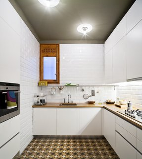 """Since the original kitchen was not functional, the architects built a new one from scratch while preserving the original tiles. """"We designed very plain oak cupboards so the floor would be the protagonist,"""" Eugeni says. Ceiling lamps by Vico Magistretti illuminate the warm wood countertops."""