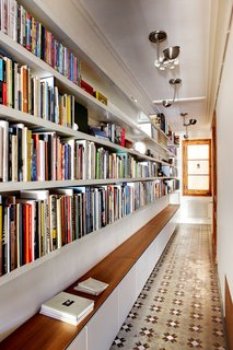 You may think that a library has to be its own room, but books can be stored and read just about anywhere. Lining a hallway with books turns it into a library that you'll walk through, and be inspired by, every day. Cabinets below provide extra storage and even a place to sit and read.