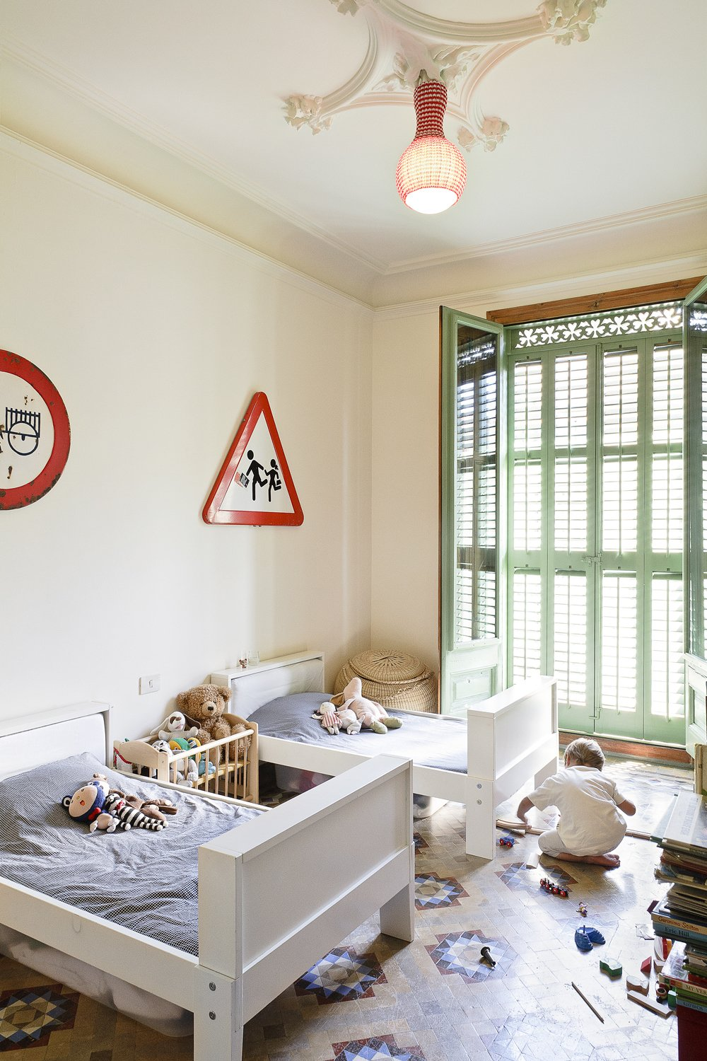 The architects' two young children occupy this bright bedroom, furnished with Ikea beds. Another custom lamp illuminates the space. Tagged: Kids Room, Bedroom, Toddler Age, Bed, and Neutral Gender.  Photo 6 of 8 in Historic Details and Playful Modernism Meet in this Stunning Barcelona Flat