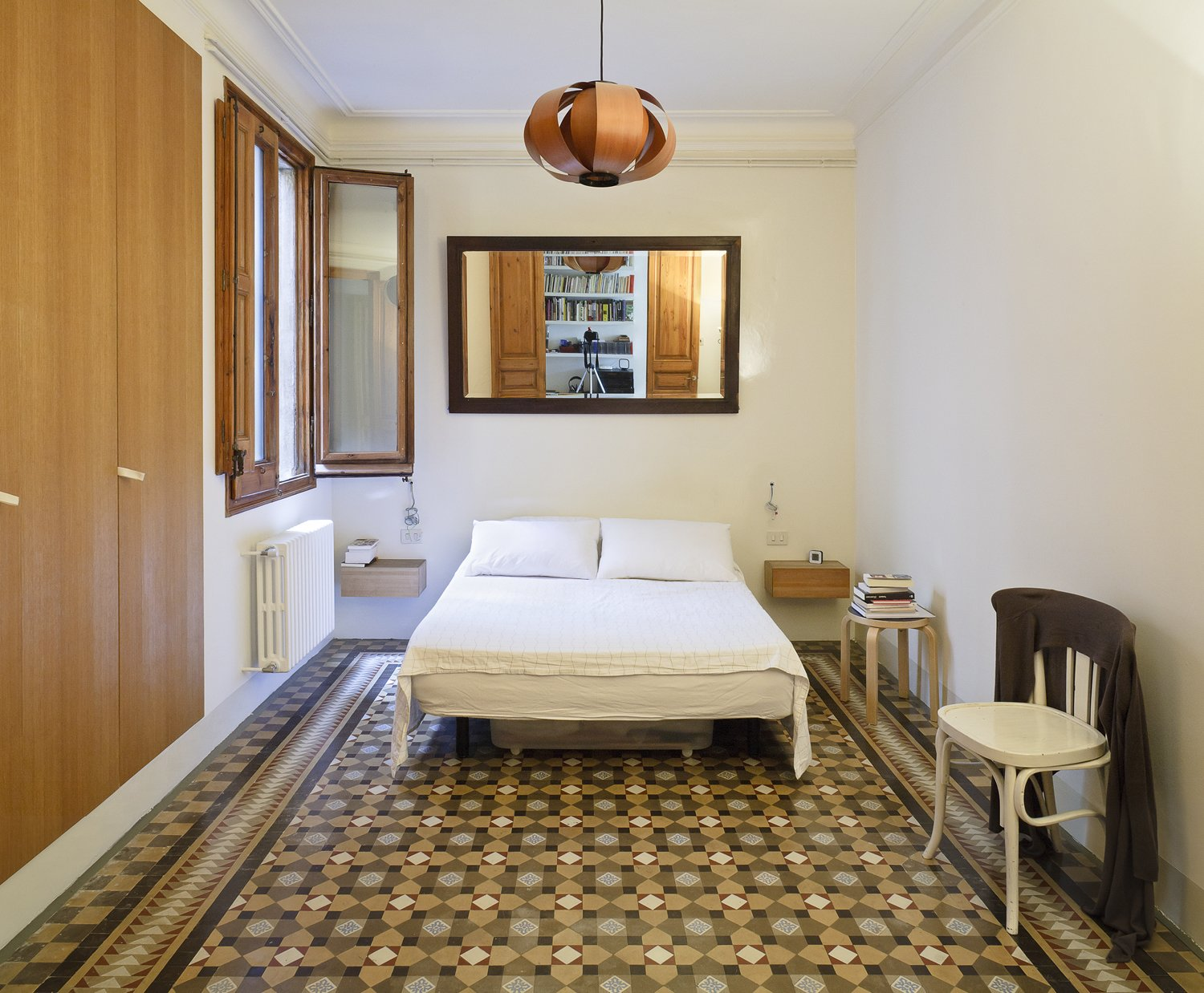 Understated décor in the master bedroom lets the floor tiles fully pop. A pendant lamp designed in 1957 by Spanish modernist architect José Antonio hangs above the bed.  Photo 7 of 8 in Historic Details and Playful Modernism Meet in this Stunning Barcelona Flat