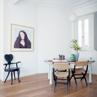 """The best way to integrate different furniture styles is to treat """"the space like a gallery and place objects according to their colors,"""" internationally acclaimed designer Jaime Hayon says. He cautions against using too much natural wood furniture in a space with wood floors: """"You need contrast."""" In his newly renovated home in Valencia, Spain, contrasting materials, small porcelain objects, and an occasional black form enliven a palette of light gray furniture. Photo by: Nienke Klunder"""