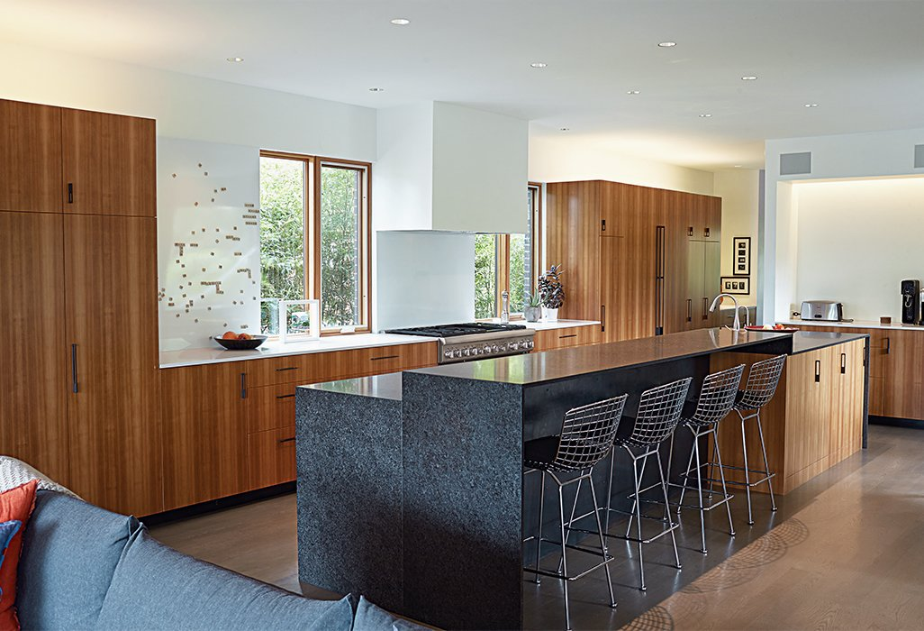 Kitchen, Wood Cabinet, Recessed Lighting, Refrigerator, Range Hood, Stone Counter, Range, and Medium Hardwood Floor In Roanoke Park, a neighborhood in Kansas City, Missouri, architect Matthew Hufft designed a home for his family that drew on the surrounding traditional homes. In the kitchen, Bertoia barstools are tucked under a custom honed-granite two-level kitchen island by a local company, Carthage Stoneworks. Hufft's team designed and built the larch cabinets. The appliances are by Thermador.  Kitchen counters from This Kansas City Home Looks Like Its Neighbors, But Reveals a Truly Modern Sensibility