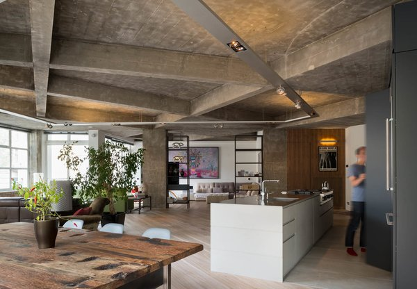 "Inside Out Architecture renovated an apartment in the Clerkenwell section of central London, removing interior walls to create an open, loft-like living space. The architects were taken in by the ""dramatic geometry"" of the existing board-formed concrete ceiling, and their design maintained and emphasized its dynamic criss-crosses and texture."