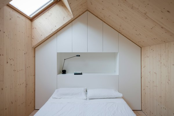Each bedroom is designed to replicated a mini house, and follows the roof's pitch. A skylight lets in light. A custom unit made of white-painted MDF panels provides necessary storage.