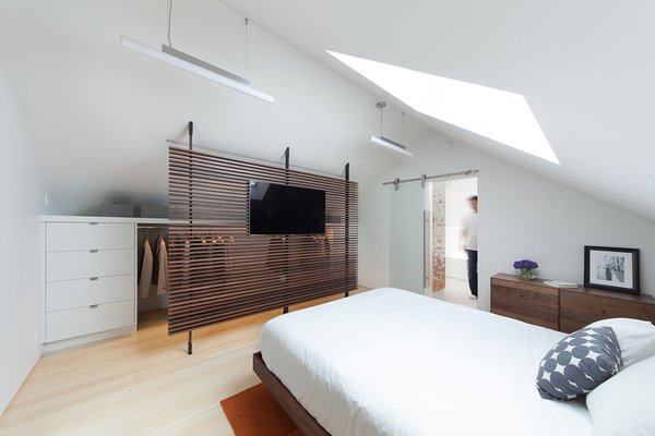 """Bedroom, Light Hardwood Floor, and Bed In the master bedroom, a small, cramped closet was replaced with a wardrobe that is partially obscured by a slatted wooden screen that was built by Metalworks & Design Studio of Seattle. """"The idea was you see through it, so in a sense it doesn't feel like a small space,"""" Smith says.  Renovations from A Musty Attic is Transformed Into a Luminous Loft"""