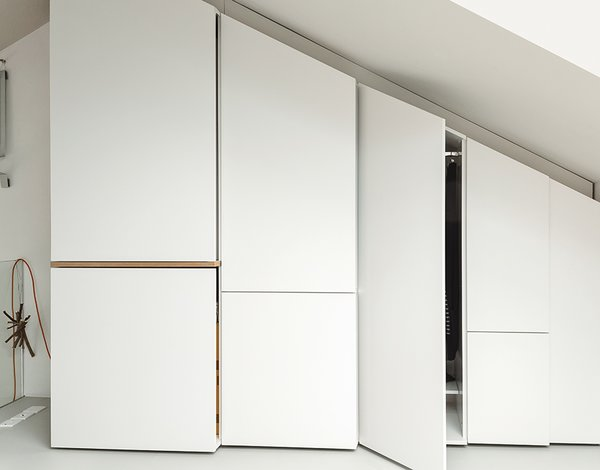 Hynam built additional storage along one angled wall of the bedroom loft and beneath the skylight.