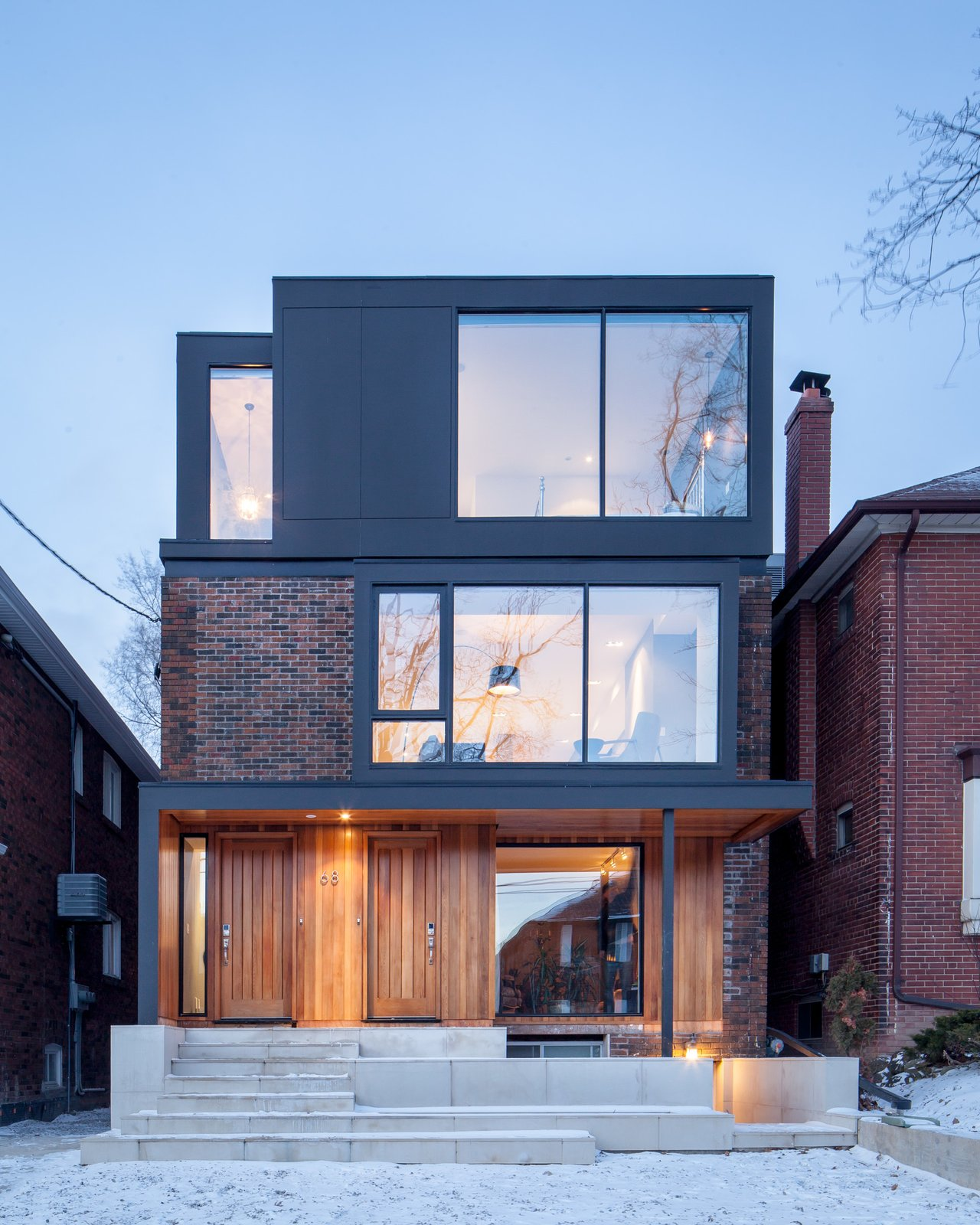 The ground floor rental unit and the owners' residence each have dedicated entrances on the front porch. The entrance's oiled cedar cladding gives the façade an added source of warmth. The basement rental unit is accessed through a separate door a few steps below the porch.  Photo 2 of 9 in A Spacious Toronto Triplex Responds to Rising Urban Density