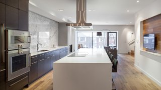 A spacious kitchen anchors the second floor. Its streamlined Cabico cabinetry and Gaggenau appliances direct the eye to the bay window and create an airy sensation. Quick meals can be eaten while perched atop the Cee stools at the Caeserstone countertop.