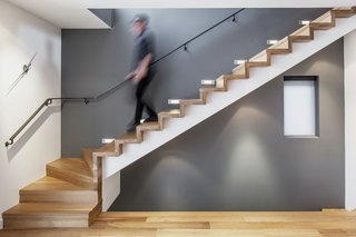 Behind the living room, a minimalist staircase leads to the upper level's bedroom and family room. White oak flooring unites the staircase and the rest of the living spaces.