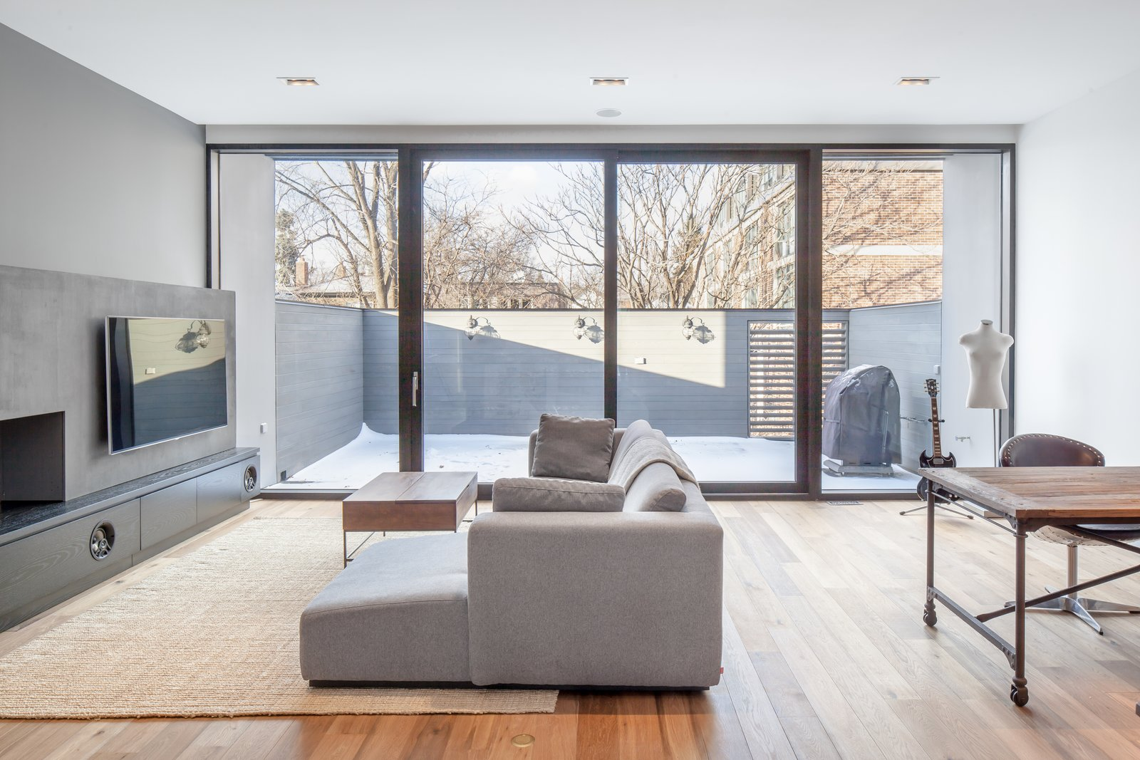 On the triplex's uppermost floor, a family room looks out onto a cantilevered terrace. Its occupants congregate to watch television on the EQ3 Morton sofa and put their feet up on the Rustic Storage coffee table by West Elm.  Photo 6 of 9 in A Spacious Toronto Triplex Responds to Rising Urban Density